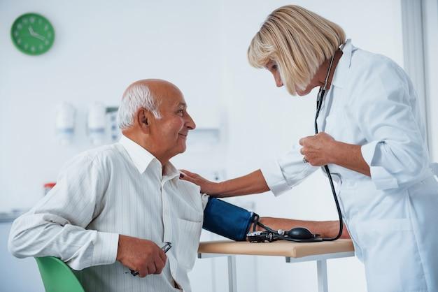 Vrouwelijke arts gebruikt tonometer om bloeddruk te meten aan senior man.