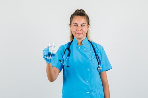 Vrouwelijke arts glas water in blauw uniform houden