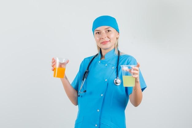 Vrouwelijke arts glazen sap houden en glimlachend in blauw uniform
