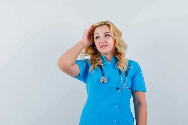 Vrouwelijke arts haar aanpassen terwijl opzij in blauw uniform kijken