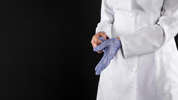 Vrouwelijke arts haar handschoenen opstijgen