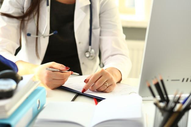 Vrouwelijke arts hand houden zilveren pen vullen