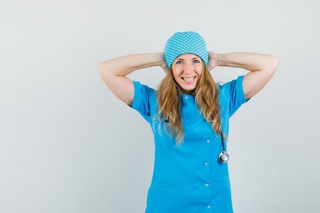 Vrouwelijke arts hand in hand achter het hoofd in blauw uniform en op zoek gelukkig.