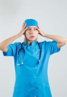 Vrouwelijke arts hand in hand in blauw uniform en kijkt geïrriteerd