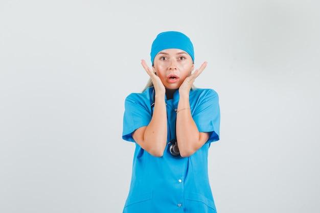 Vrouwelijke arts hand in hand in de buurt van gezicht in blauw uniform en bang op zoek