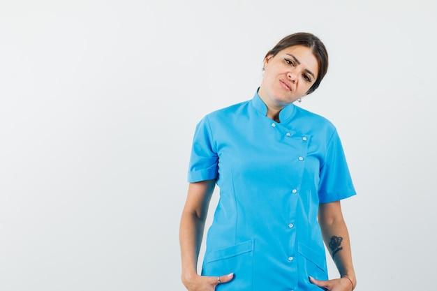 Vrouwelijke arts hand in hand in zakken in blauw uniform en ziet er zelfverzekerd uit