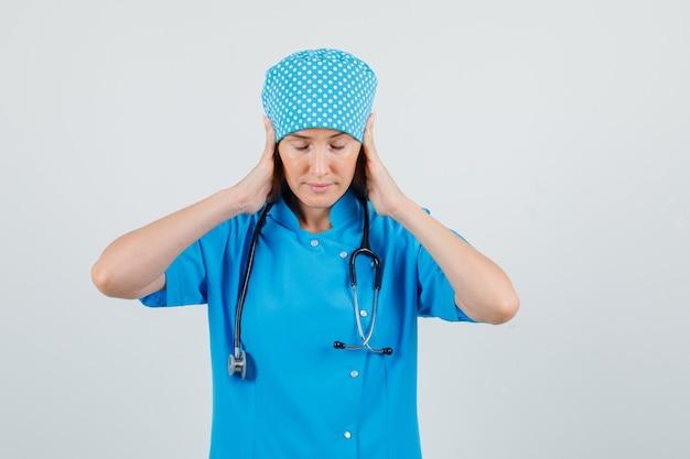 Vrouwelijke arts hand in hand op de oren terwijl ze in blauw uniform neerkijkt en er moe uitziet