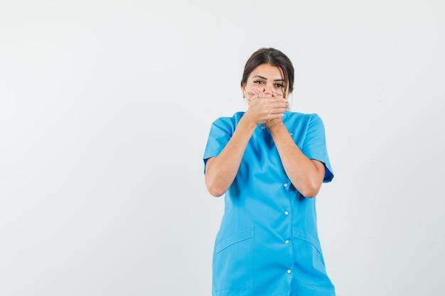 Vrouwelijke arts hand in hand op mond in blauw uniform en ziet er bang uit