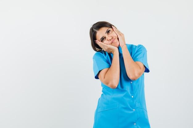 Vrouwelijke arts hand in hand op wangen in blauw uniform en ziet er schattig uit