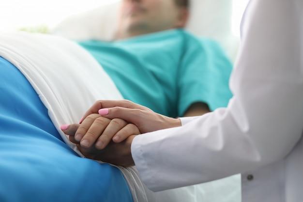Vrouwelijke arts handen houden mannelijke arm in medisch ziekenhuis