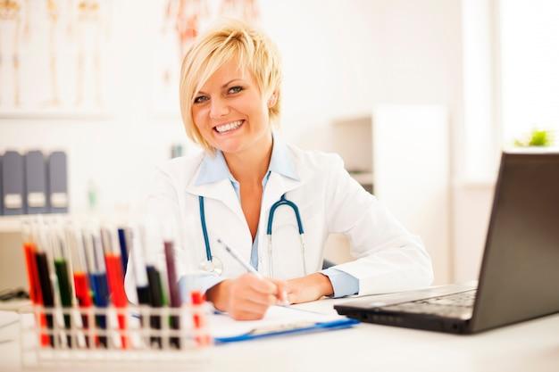 Vrouwelijke arts hard aan het werk in haar kantoor