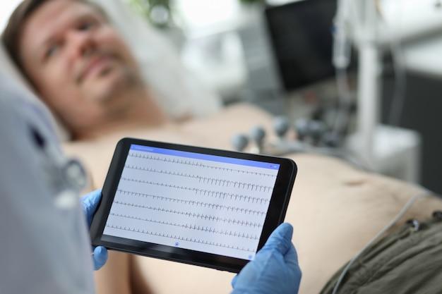 Vrouwelijke arts houdt tablet met elektrocardiogram
