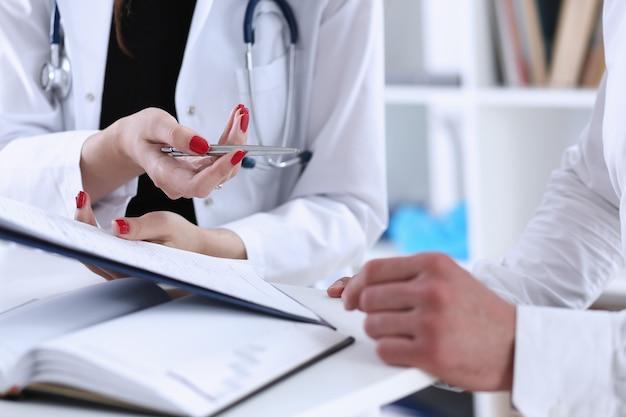 Vrouwelijke arts houdt zilveren pen vast en toont pad