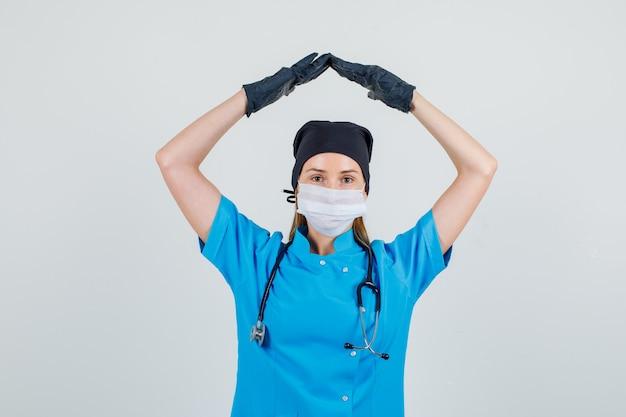 Vrouwelijke arts huis dak boven het hoofd gebaren in uniform, handschoenen, masker vooraanzicht.