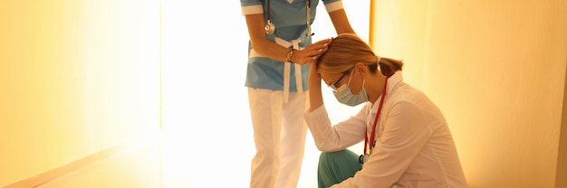Vrouwelijke arts in beschermend medisch masker zit in gang met haar hoofd verlaagd en haar collega ondersteunt haar. medische fout in geneeskundeconcept