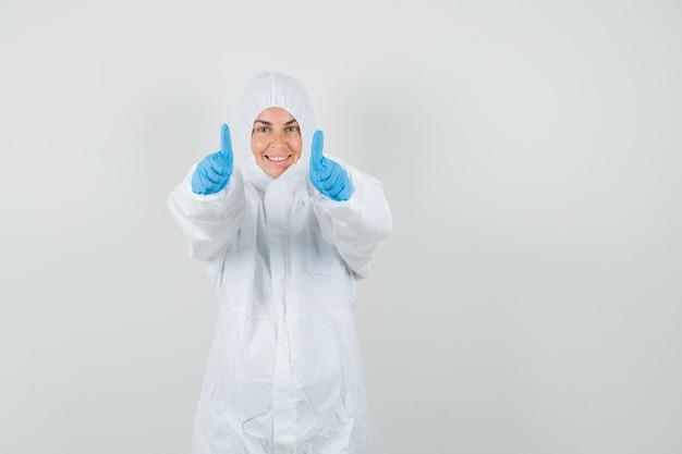 Vrouwelijke arts in beschermend pak, handschoenen die dubbele duimen tonen en gelukkig kijken