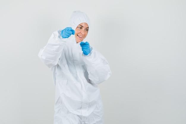 Vrouwelijke arts in beschermend pak, handschoenen die op camera richten en vrolijk kijken