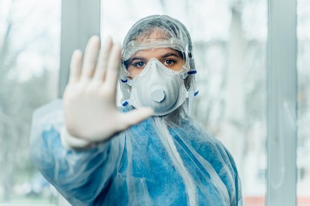 Vrouwelijke arts in beschermend pak tegen de ziekte