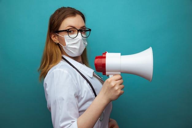 Vrouwelijke arts in beschermingskostuum en glazen met masker houdt megafoon.