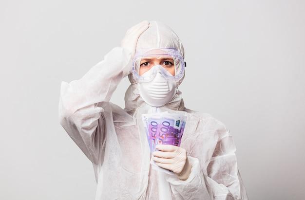 Vrouwelijke arts in beschermingspak en bril met masker houdt euro geld