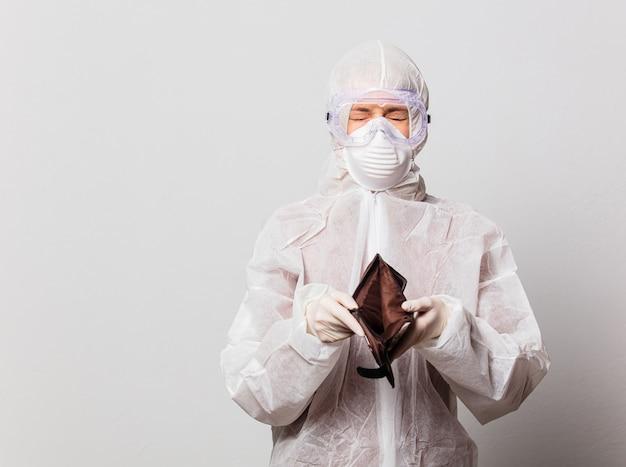 Vrouwelijke arts in beschermingspak en bril met masker houdt lege portemonnee