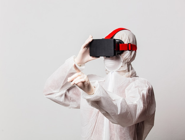 Vrouwelijke arts in beschermingspak en vr-bril met masker