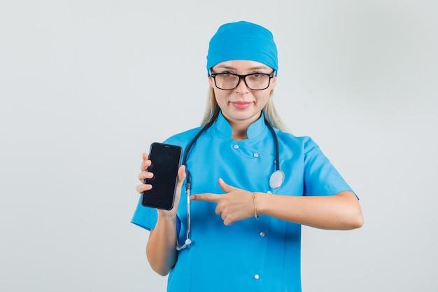 Vrouwelijke arts in blauw uniform, bril wijzende vinger naar smartphone en op zoek vrolijk