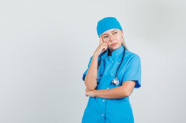Vrouwelijke arts in blauw uniform denken met vingers op de wang en peinzend op zoek