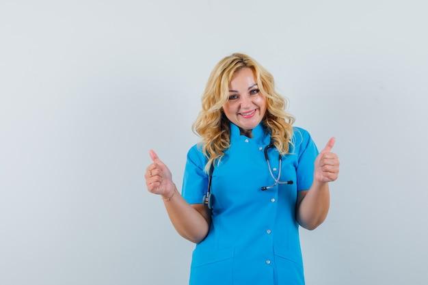Vrouwelijke arts in blauw uniform die duim toont en blij kijkt