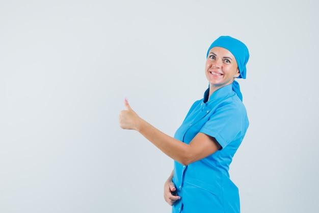 Vrouwelijke arts in blauw uniform die duim toont en vreugdevol, vooraanzicht kijkt.