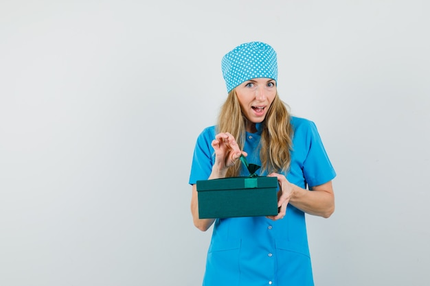 Vrouwelijke arts in blauw uniform die giftdoos probeert te openen en nieuwsgierig kijkt