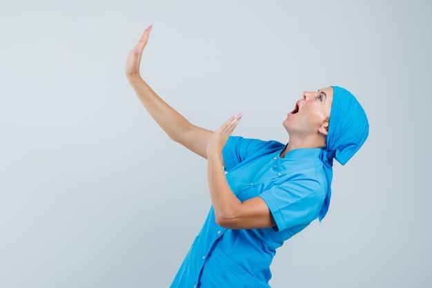 Vrouwelijke arts in blauw uniform die handen opheft om zichzelf te verdedigen en bang, vooraanzicht kijkt.