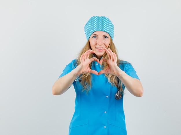 Vrouwelijke arts in blauw uniform die hartgebaar toont en vrolijk kijkt