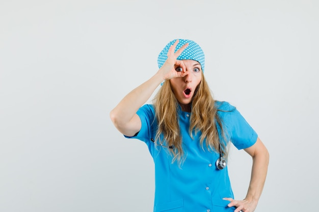 Vrouwelijke arts in blauw uniform die ok teken op oog toont en verbaasd kijkt