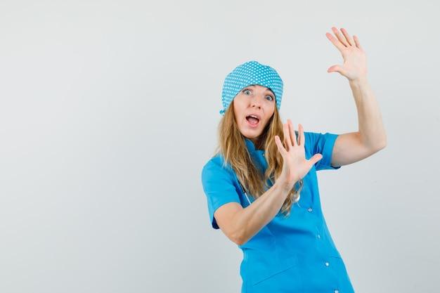 Vrouwelijke arts in blauw uniform die palmen opheft om zich te verdedigen en bang kijkt