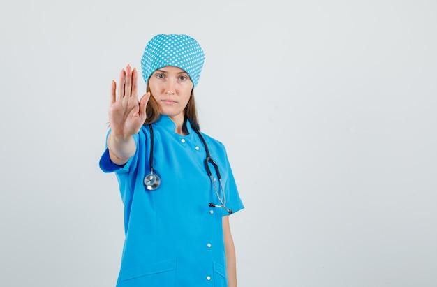 Vrouwelijke arts in blauw uniform die stopgebaar toont en ernstig, vooraanzicht kijkt.