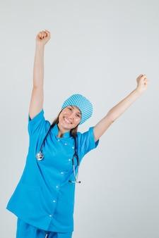 Vrouwelijke arts in blauw uniform die vuisten opheft en vrolijk kijkt