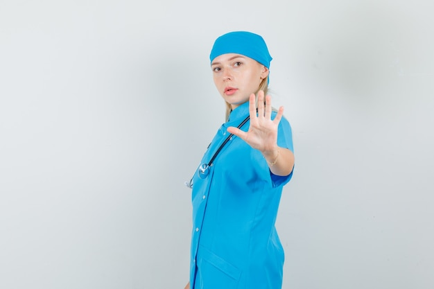 Vrouwelijke arts in blauw uniform die weigeringsgebaar met hand tonen en ernstig kijken.