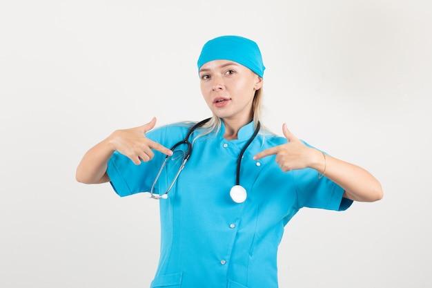 Vrouwelijke arts in blauw uniform die zich met vingers toont en trots kijkt