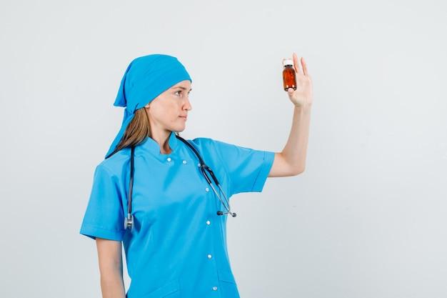 Vrouwelijke arts in blauw uniform drug fles te houden en op zoek ernstig