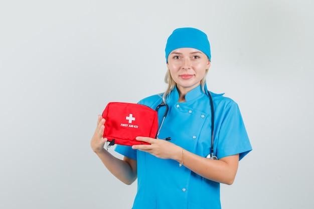 Vrouwelijke arts in blauw uniform ehbo-kit houden en vrolijk kijken