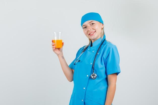 Vrouwelijke arts in blauw uniform glas sap houden en vrolijk kijken