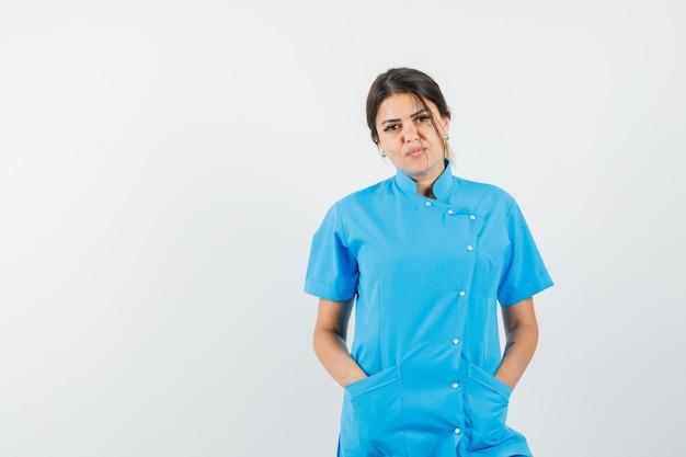 Vrouwelijke arts in blauw uniform hand in hand in zakken en ziet er zelfverzekerd uit