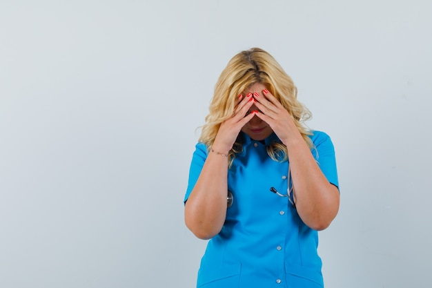 Vrouwelijke arts in blauw uniform hand in hand op voorhoofd en op zoek naar angstige ruimte voor tekst