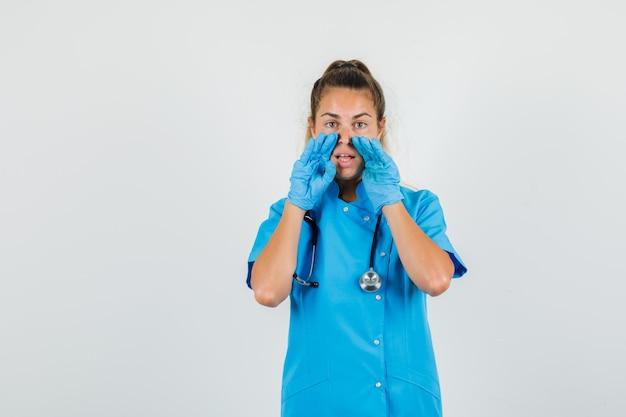 Vrouwelijke arts in blauw uniform, handschoenen die iets vertrouwelijks vertellen en nieuwsgierig kijken