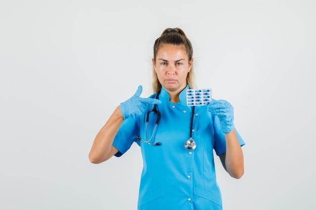 Vrouwelijke arts in blauw uniform, handschoenen wijzend op pakje capsules en er serieus uitzien