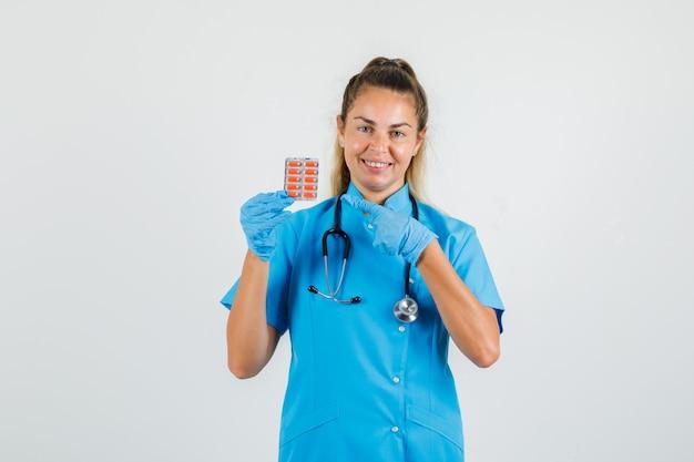 Vrouwelijke arts in blauw uniform, handschoenen wijzend op pakje pillen en op zoek vrolijk