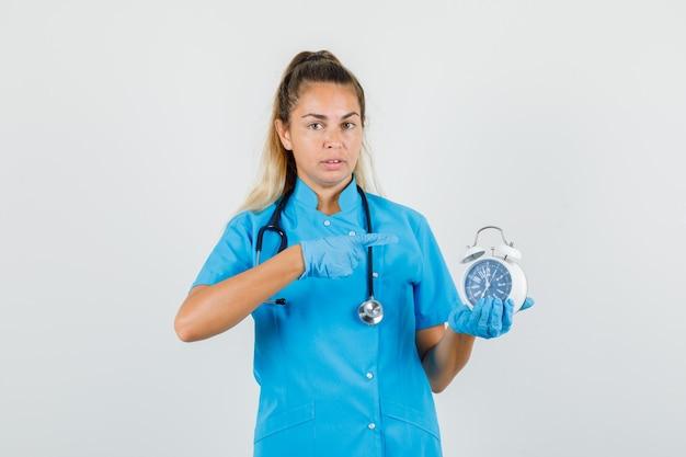 Vrouwelijke arts in blauw uniform, handschoenen wijzende vinger op wekker
