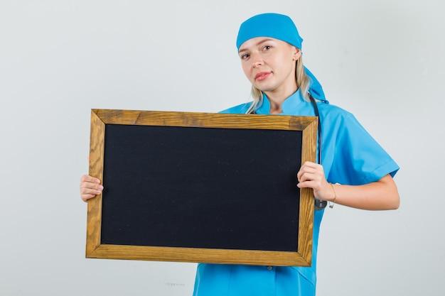 Vrouwelijke arts in blauw uniform houden bord en glimlachen