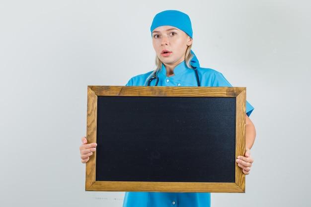 Vrouwelijke arts in blauw uniform houdt bord en kijkt bezorgd